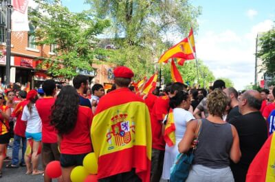 Crowd of people, some of whom are draped in Spanish flags